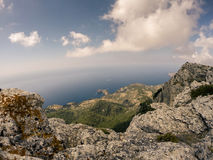 Rocky beaches on the northern part of Mallorca island, Spain. Tramuntana mountains with green trees and bushes and blue sea in distance. Tourist destination Stock Images