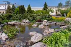 A rocky bottom of an artificial lake with a cascading fountain on a botanical sunny day stock photography