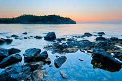 Rocky bottom of the sea and the sunrise. Over the mountains Royalty Free Stock Image