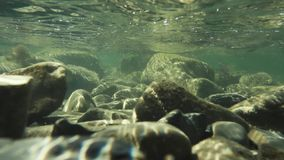 Rocky bottom and sunbeams under water slow motion stock video
