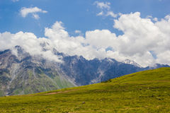 Rocky Caucasus berg i den Kazbeki regionen med molnig blå himmel Arkivfoton