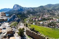 Road view from the cliff. Rocky cliff above the clear clear Sea and village, View from View Point, Sudak, Crimea stock photography