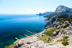 Sea view from the cliff. Rocky cliff above the clear clear Sea and village, View from View Point, Sudak, Crimea Royalty Free Stock Images