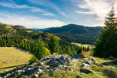 Rocky cliff above the forested valley. Beautiful autumn sunrise in mountainous landscape stock images