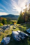 Rocky cliff above the forested valley. Beautiful autumn sunrise in mountainous landscape stock photography
