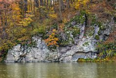 Rocky cliff above the river in autumn forest. Stunning nature scenery Royalty Free Stock Photography