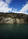 Rocky Cliff with Blue Skies and Green Water. Image of the Island of the Birds in Puerto Natales, Chile. Image is lit with bright sunlight peeking through clouds stock image