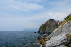 Rocky cliff and buildings in Manarola Royalty Free Stock Photography