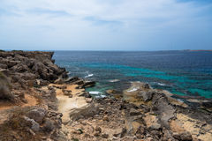 Rocky cliff. And crystal clear sea water Stock Photos