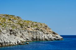 Rocky cliff at the edge of the Mediterranean Sea. On the island of Rhodes Royalty Free Stock Photo