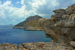 Rocky cliff at the edge of the Mediterranean Sea. On the island of Rhodes Royalty Free Stock Photos