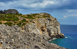 Rocky cliff at the edge of the Mediterranean Sea. On the island of Rhodes Stock Photography