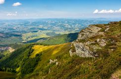 Rocky cliff on the edge of mountain hill. Gorgeous view in to the valley on fine summer day Stock Photo