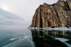 Rocky cliff on frozen lake Stock Photo
