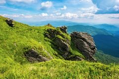 Rocky cliff on a grassy slope stock photos