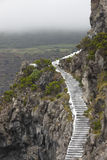 Rocky cliff landscape with ancient stairs in a foggy day Royalty Free Stock Photos
