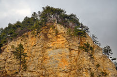 A rocky cliff with a layered structure of sedimentary rocks Stock Photo