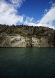 Rocky Cliff met Blauwe Hemel en Groen Water Stock Afbeelding
