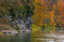 Rocky cliff of mountain river background. In autumn. colorful forest foliage reflects on a rippled water surface Stock Image