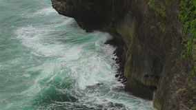 A rocky cliff and ocean waves