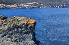Rocky cliff with orange lichen. On the edge of the blue ocean royalty free stock photos