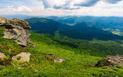 Rocky cliff over the grassy valley. Beautiful summer landscape with mountain ridge in the distance Stock Images