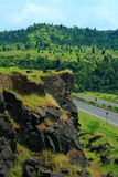 Rocky cliff over a highway and mountain Stock Photos