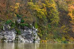 Rocky cliff over the river in forest. Beautiful autumn background with lots of textures Royalty Free Stock Photo