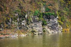 Rocky cliff over the river in forest. Beautiful autumn background with lots of textures Stock Images