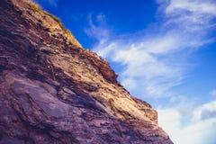 Rocky cliff side against blue sky Stock Photos