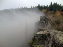 Rocky cliff side. A foggy view over a rocky cliff edge Royalty Free Stock Photography