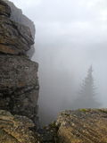 Rocky cliff side. A foggy view over a rocky cliff edge Stock Images