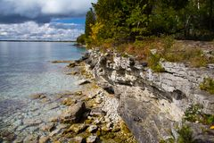 Rocky Cliff Walls of Cave Point Park, Door County. Pale dolomite cliff walls covered with cedar forest are slowly eroded by Lake Michigan waves at Cave Point Royalty Free Stock Photos