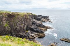 Rocky cliffs along Wild Atlantic Way tourist route on Irish west. Rocky cliffs along Wild Atlantic Way dramatic and scenic tourist route on Irish west coast Royalty Free Stock Image