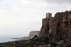 Rocky cliffs with an ancient tower, cloudy sky Stock Images