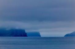 Rocky cliffs behind clouds, Alaska, USA. Misty landscape of rocky cliffs behind low clouds, Prince William Sound, Alaska, USA Stock Images