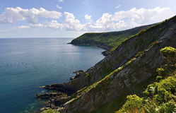 Rocky cliffs covered in grass with sea Stock Photography