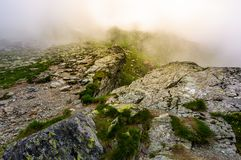 Rocky cliffs of Fagaras mountains in fog. Fantastic atmosphere of mysterious scenery of Romania Carpathians in summer. sun is shining behind the haze Royalty Free Stock Images
