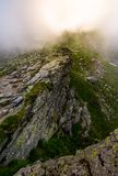 Rocky cliffs of Fagaras mountains in fog. Fantastic atmosphere of mysterious scenery of Romania Carpathians in summer. sun is shining behind the haze Stock Image