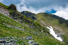 Rocky cliffs on grassy slopes with snow in summer. Lovely nature scenery under the cloudy sky in Fagaras mountains, Romania Royalty Free Stock Photos