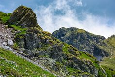 Rocky cliffs on grassy slopes with snow in summer. Lovely nature scenery under the cloudy sky in Fagaras mountains, Romania Stock Photo