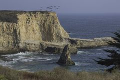 Rocky Cliffs Meet the Sea at Santa Cruz, California. A squadron of pelicans emerges above the rocky cliffs that jut into Monterey Bay at Santa Cruz, California royalty free stock photography