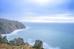 Portugal Long Exposure Atlantic Ocean Seascape. Rocky cliffs on Portuguese Atlantic Ocean with big waves and fast moving stormy clouds shot as long exposure Stock Images