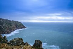 Portugal Long Exposure Atlantic Ocean Seascape. Rocky cliffs on Portuguese Atlantic Ocean with big waves and fast moving stormy clouds shot as long exposure Stock Photos