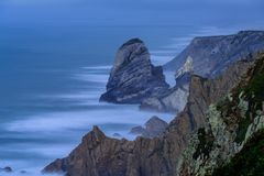 Portugal Long Exposure Atlantic Ocean Seascape. Rocky cliffs on Portuguese Atlantic Ocean with big waves and fast moving stormy clouds shot as long exposure Stock Photo