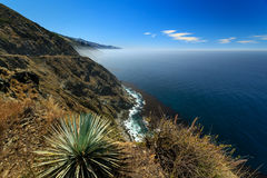 Rocky cliffside coastline along pacific ocean Stock Images