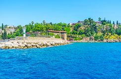 Antalya from the sea. The rocky coast of Antalya with lush greenery on the slopes, massive ramparts, modern lighthouse and numerous tourists, walking there Royalty Free Stock Photo