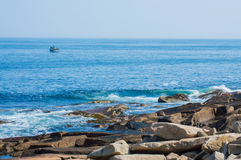 Rocky coast at the Atlantic ocean with fishing boat in the distance Royalty Free Stock Image