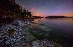 Rocky Coast bij nacht met Purpere Hemel Stock Foto's