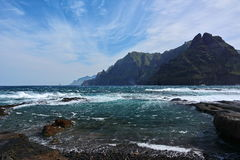 Rocky coast, blue sky, waves  and mountains Royalty Free Stock Images